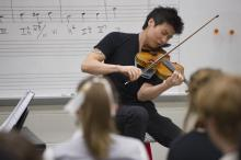 A man performs on the violin in a classroom while students watch.