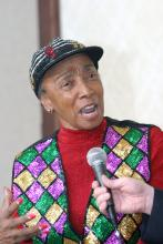 A woman wearing a red shirt and brightly sequined hat and vest speaks into a microphone.