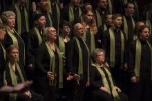 a chorus stands and sings