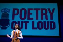 A young woman speaks at a microphone with the Poetry Out Loud logo on a screen behind her.