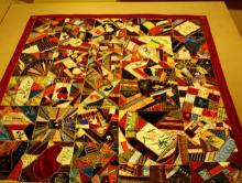 photo of a multi-colored pieced crazy quilt with a red border