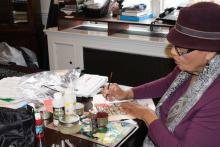 an older African American woman in a purple hat painting in colors on an art work in progress