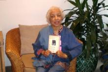Ruby Dee on her couch holding up a copy of Ernest Gaines A Lesson Before Dying