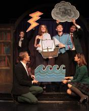Six actors performing, holding cut outs of waves, a ship, clouds, and lightning