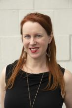 A woman with red hair stands against a white wall.