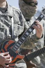 Male in uniform playing a guitar.