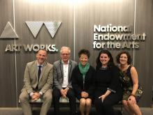 2 white men, an asian woman, and 2 white women  sit on a bench against a background that has the NEA  logo