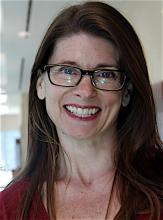 a white woman with long brown hair and glasses