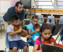A teaching artist works with three students learning the violin.