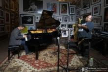 A man plays piano and another plays saxophone in a small art gallery