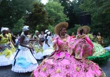 a parade of women in brilliantly colored costumes featuring wide hoop-like skirts that are heavily decorated