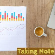 photo of graphs and charts with a cup of coffee and text that reads Taking Note