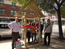 Two teens cut a ribbon on a newly installed arrow sculpture while two adult men stand smiling at the camera