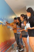 Four young Native American girls in casual clothing paint a mural in blue, yellow, and orange on an office wall
