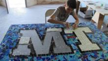 Boy at a table assembling a mosaic with the letters MT.