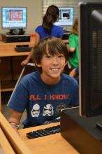 A young boy sits in the front of a computer with other students working on computers in the background.