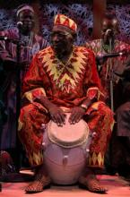A man in a brightly colored red and yellow outfit plays a large drum with his hands.