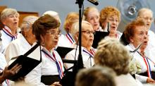 A group of older adult women singing in a chorus