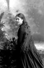 a black and white photo from the early 20th century of a young white woman with long dark hair and Victorian dress