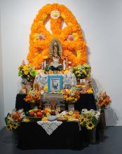 An altar made with flowers against a wall.