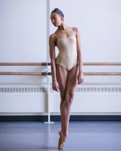 A woman in a leotard adops a dance pose.