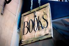 weathered hanging sign that says books in capital letters