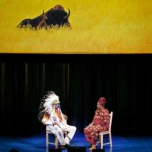 A man in Native American regalia sits on a stage across from a woman. An image of a buffalo is on the screen behind them.