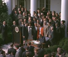 Large group of men and women surrounding President Johnson sitting at a small table signing the legislation