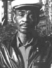 Black and white photo of a man wearing a hat