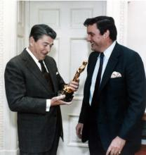 President Ronald Reagan holds an Oscar statuette while Frank Hodsoll looks on