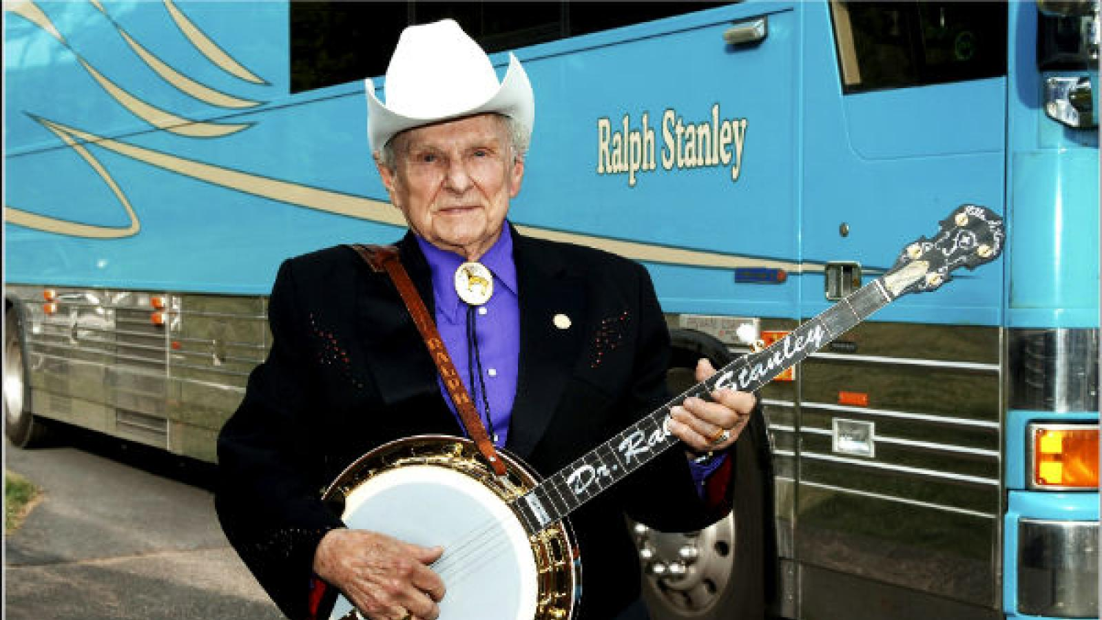 Ralph Stanley, bluegrass musician standing in front of his band's tour bus