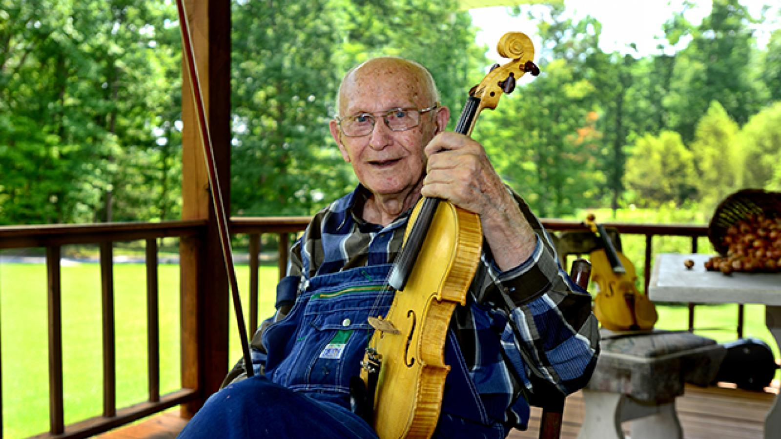 A man sits on a porch wearing overalls and holding a fiddle