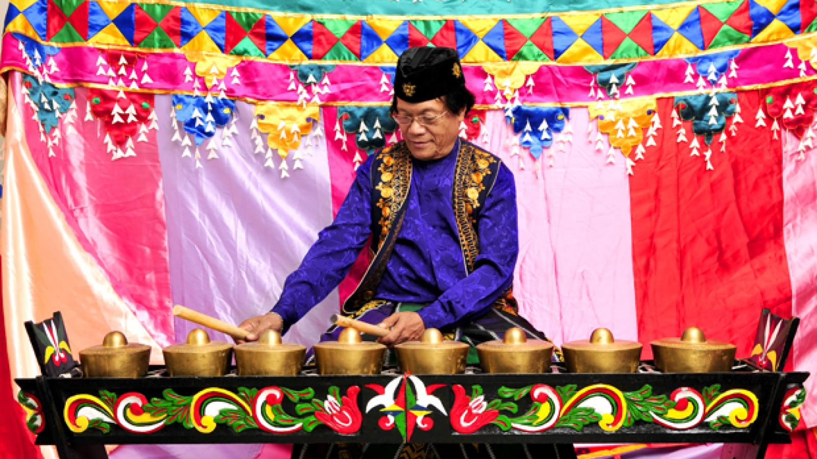 A man in a purple shirt and gold and black vest sits behind a musical instrument made up of eight small gongs.