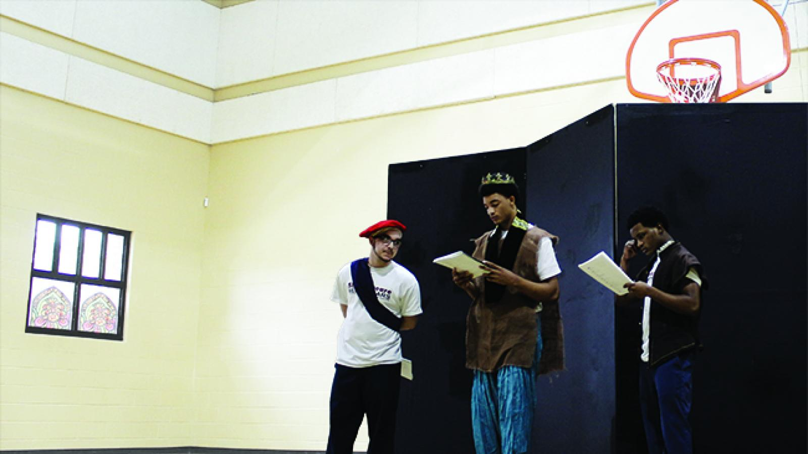 Three young men wearing costumes read from scripts in a gymnasium