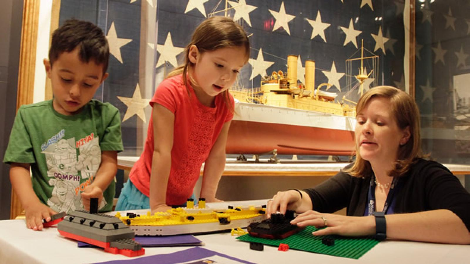 Woman with two children at a table buildig lego ships