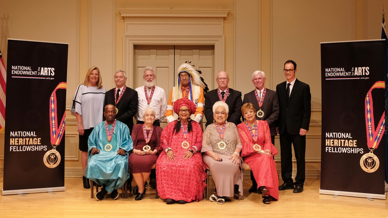 Group of folk artists posing for photo with NEA chairman at left and Folk Arts Director at right.