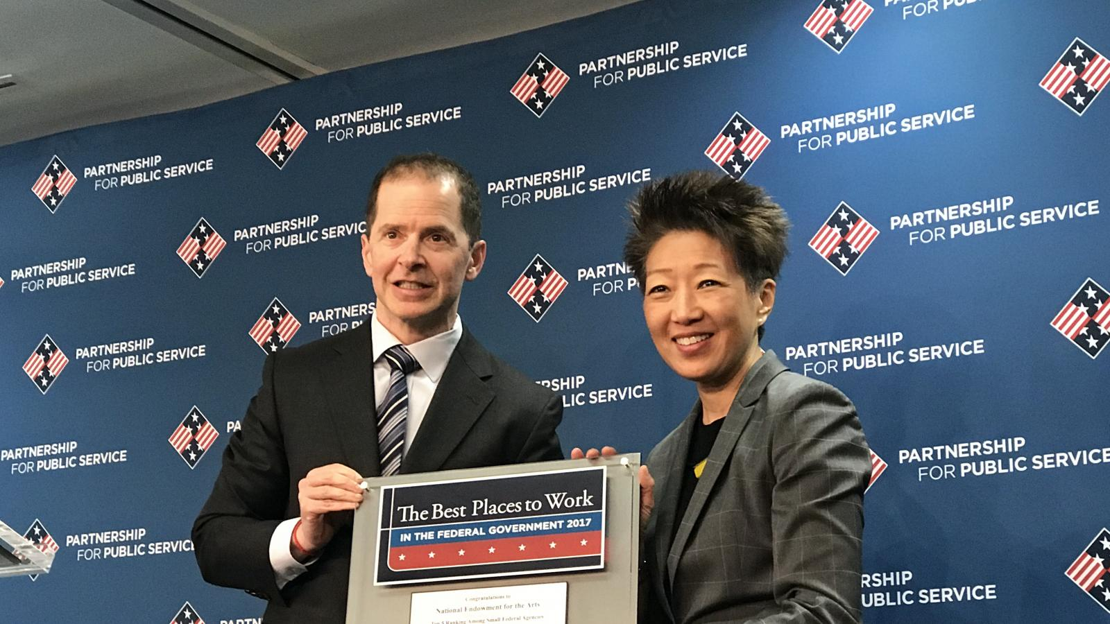 "A man and a woman pose holding a plaque which says ""The Best Places to Work in the Federal Government 2017"""