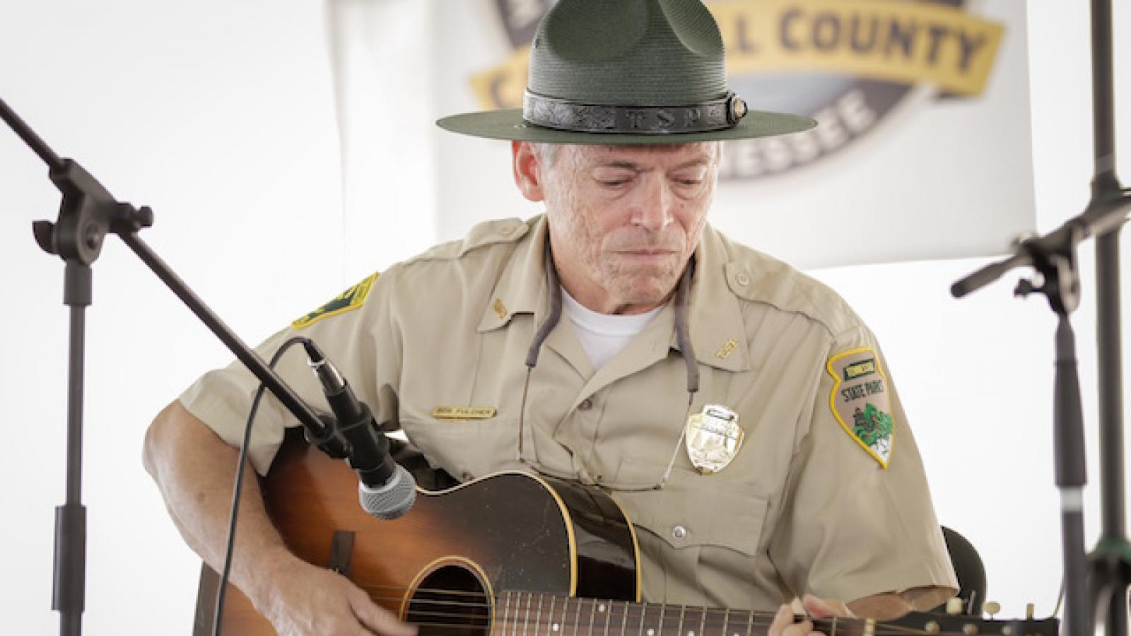 Bob Fulcher in his state parks uniform sits on a chair playing the guitar