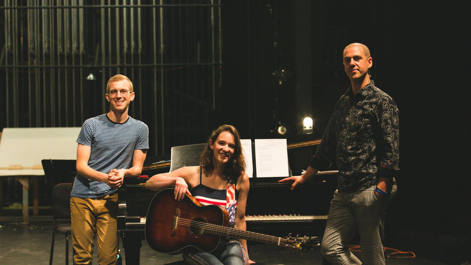 A young woman sits on a piano bench holding a guitar while two men stand casually leaning on the piano
