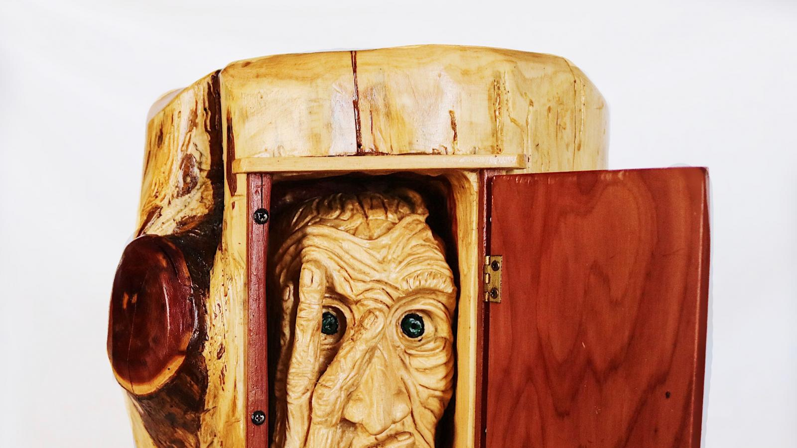 wood carving of a wrinkled face inside a log