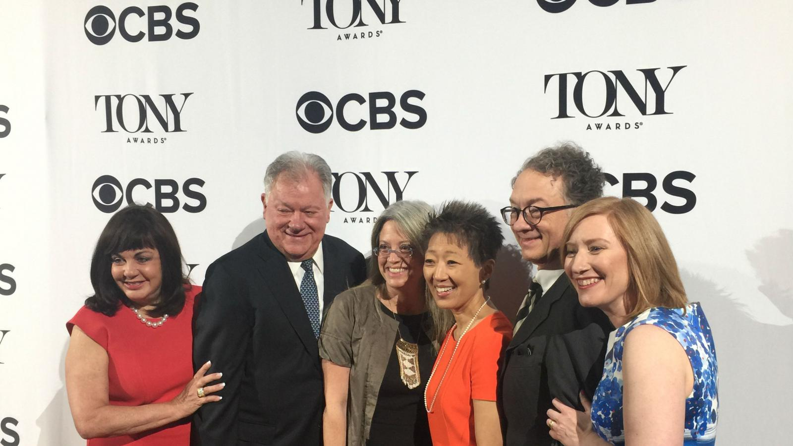 6 people in group in front of banner with Tony Awards and CBS logos