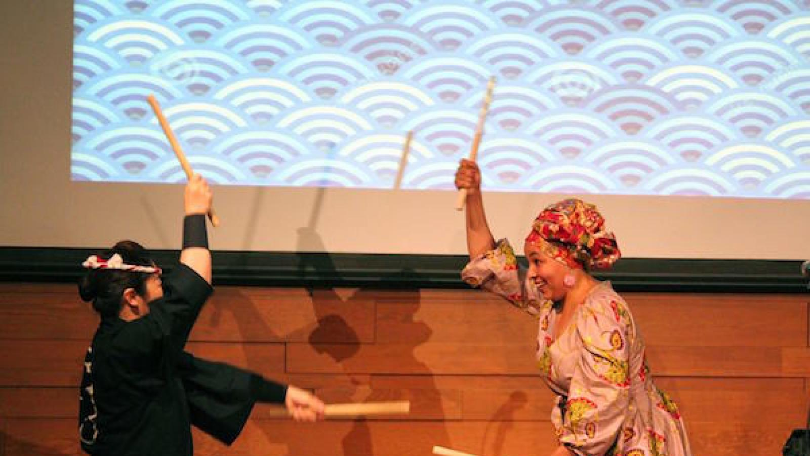 two women play a taiko drum standing on either side of it