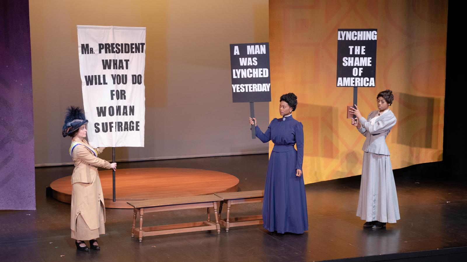 Actresses hold up picket signs about suffrage and lynching