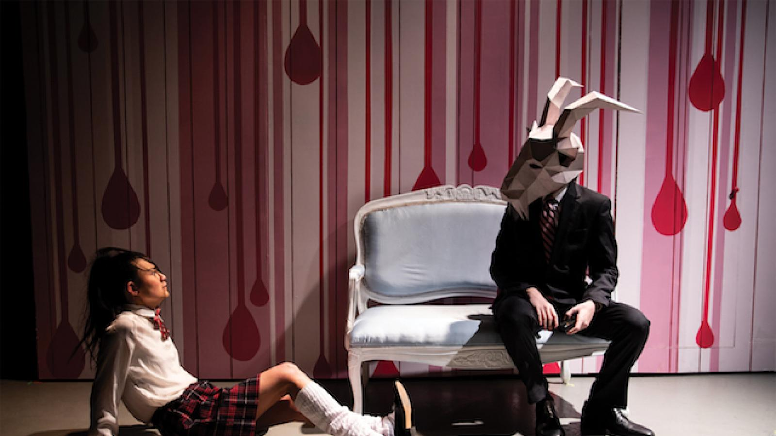 a girl in a school uniform sits on the floor looking up at a person sitting on a couch wearing an animal head