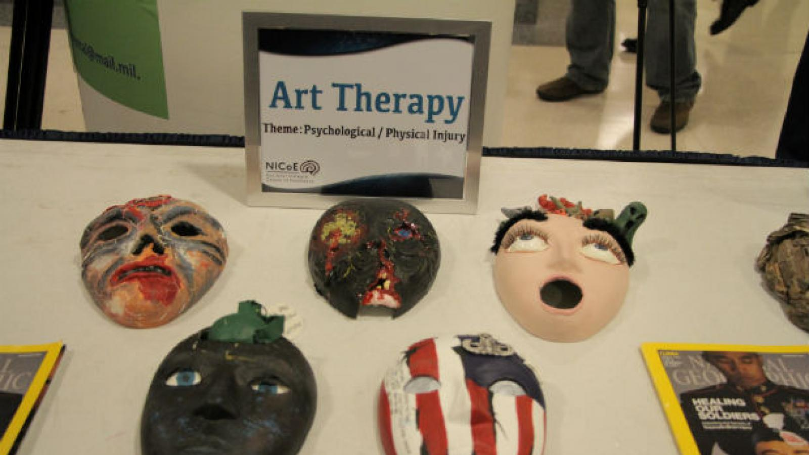 theater masks created by service members on display table