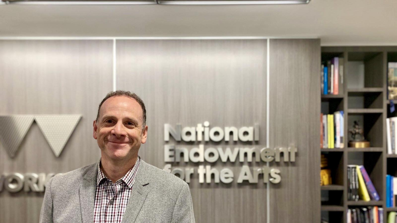 man smiling in front of National Endowment for the Arts sign