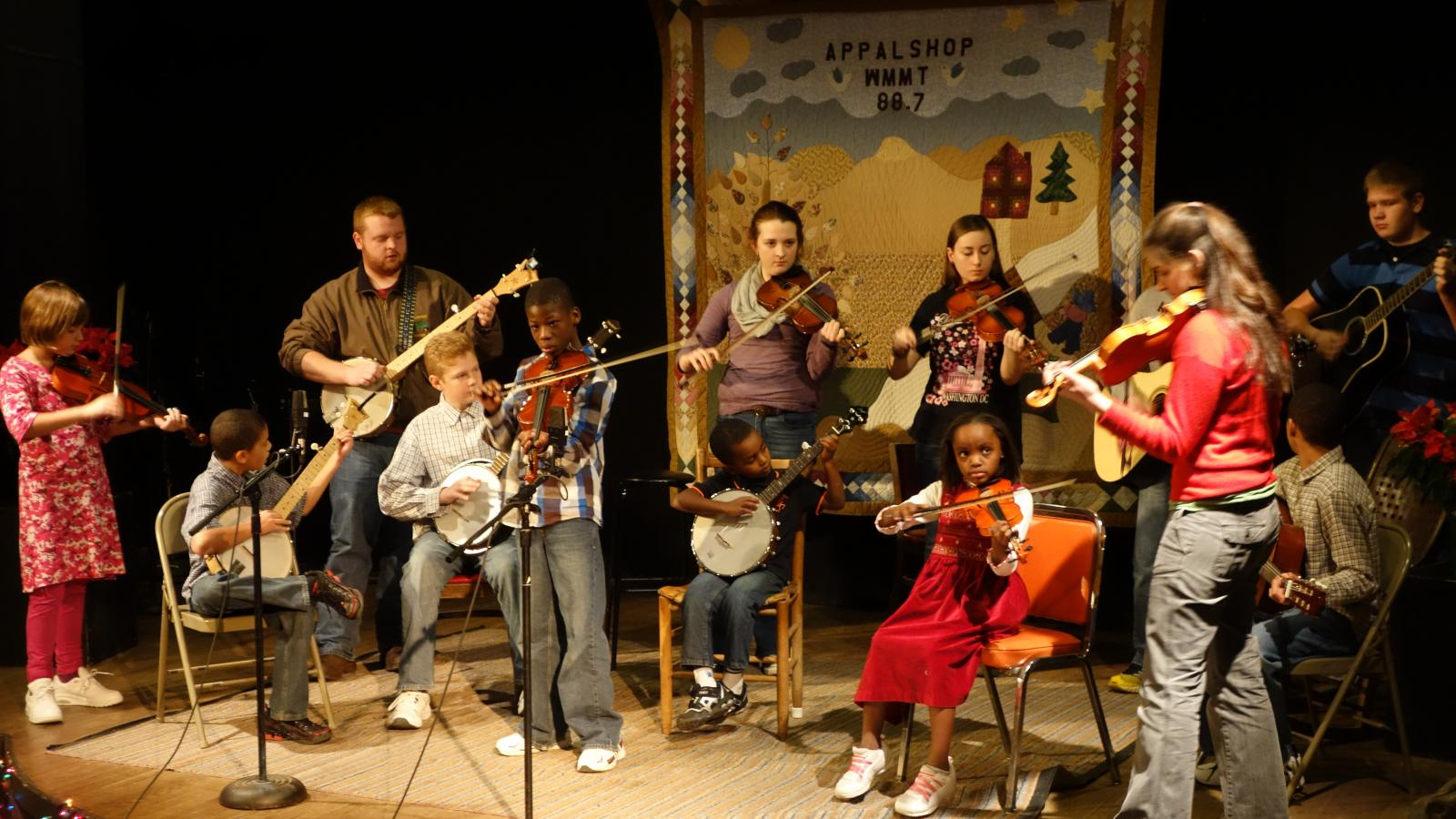 Small stage with young people playing musical instruments