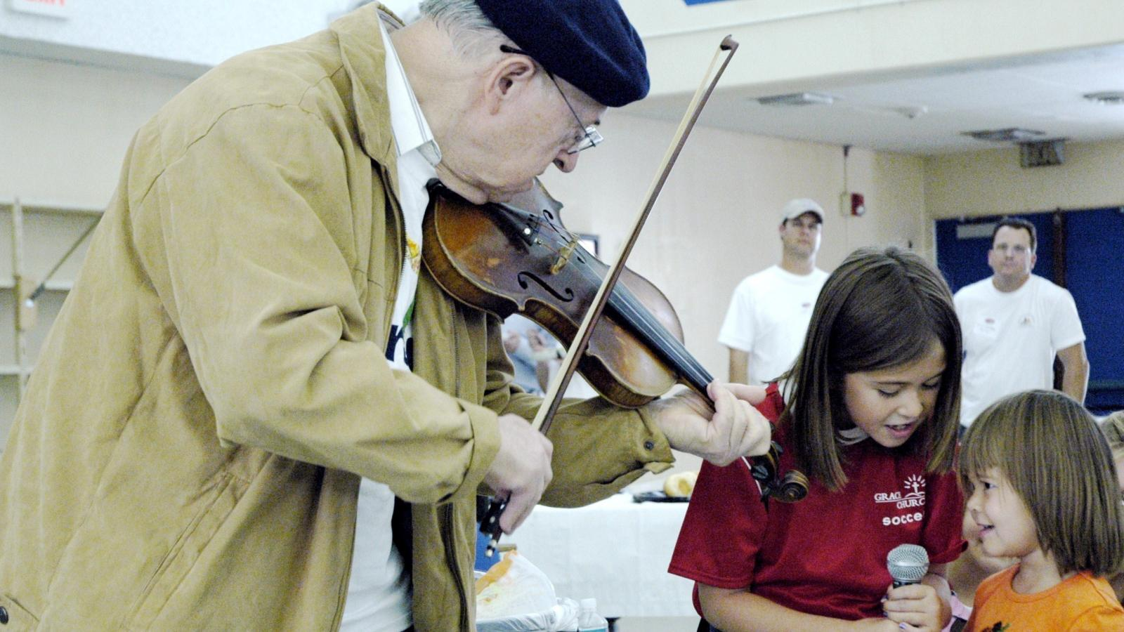 Older man plays violin to two girls