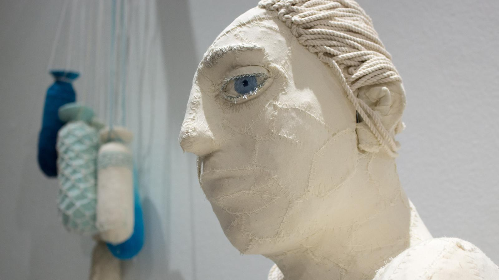 A white bust of a woman with one giant blue eye