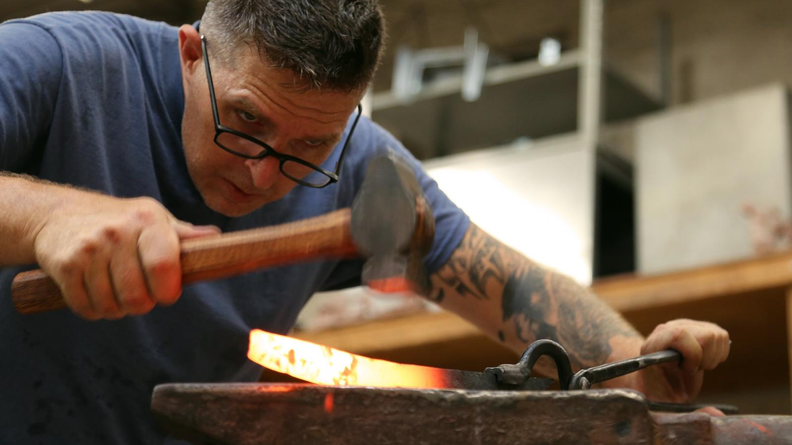 Man looks closely at a blade he is forging